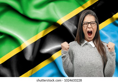 Ecstatic woman holidng fists and screaming against flag of Tanzania