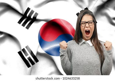 Ecstatic woman holidng fists and screaming against flag of South Korea