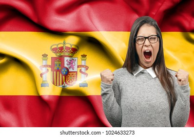 Ecstatic woman holidng fists and screaming against flag of Spain