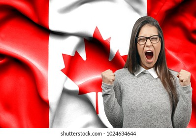 Ecstatic woman holidng fists and screaming against flag of Canada