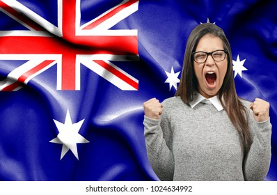 Ecstatic woman holidng fists and screaming against flag of Australia