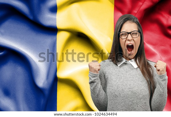 Ecstatic woman holidng fists and screaming against flag of Romania