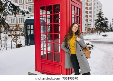 Ecstatic woman in trendy yellow sweater posing with pleasure next to red phone booth in winter. Outdoor photo of relaxed caucasian girl with brown backpack having fun in England in january.