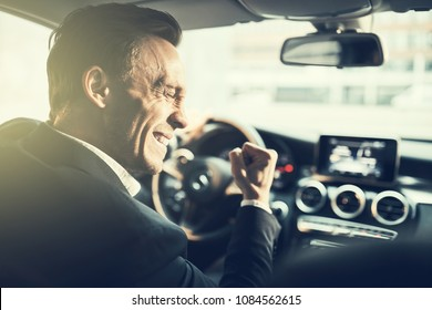 Ecstatic young businessman celebrating success with a fist pump while driving to work in is car during his morning commute