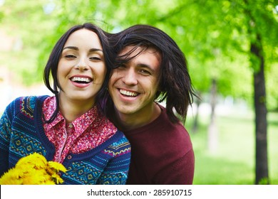 Ecstatic young couple looking at camera in park