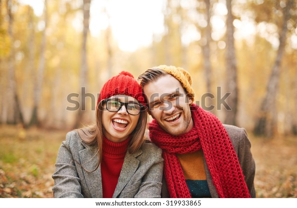 Ecstatic young dates in warm jackets and knitted caps looking at camera outdoors