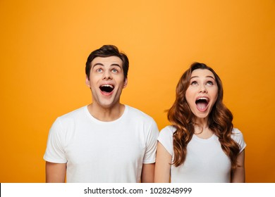 Ecstatic young man and woman in white t-shirts looking upward in excitement with open mouth, isolated over yellow background