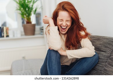 Ecstatic young woman cheering in jubilation and laughing as she sits on a sofa at home