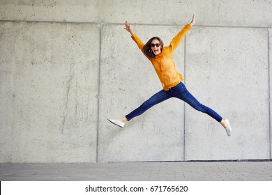 Ecstatic young woman jumping in joy and raising arms in urban outside setting