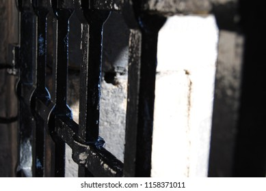 ECU of an old black metal gate on a sunny day.