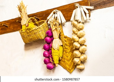 Ecuador. Garlic, mais cob, and onions are hanging on a wall.