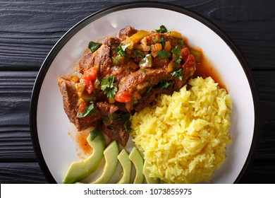 Ecuadorian seco de chivo stewed goat meat with a side dish of yellow rice and avocado close-up on a plate on the table. horizontal top view from above