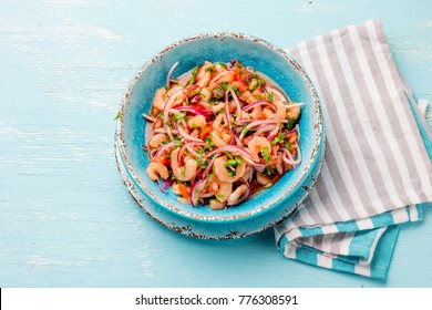 Ecuadorian shrimps ceviche sebiche with tomatoes in blue bowl, wooden blue background. Traditional ecuadorian colombian or mexican dish