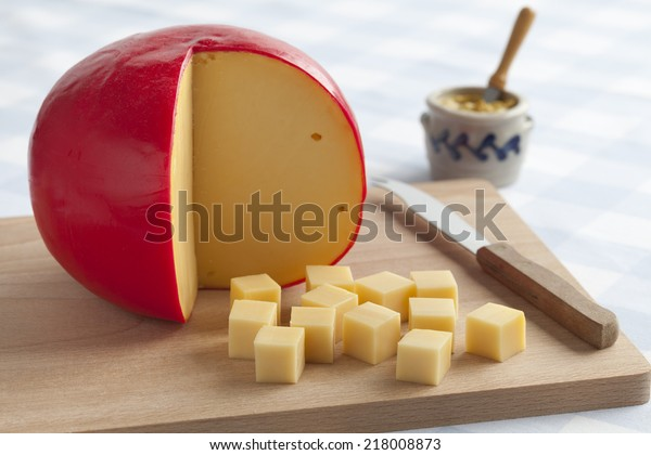 Edam cheese and cubes on a cutting board