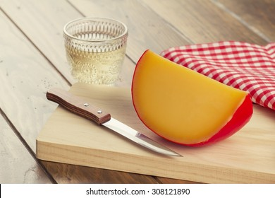 Edam cheese, a glass of wine, a red checkered napkin and a knife on a wooden table