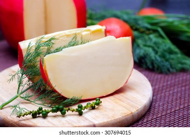 Edam cheese and a piece with fennel and tomatoes on a cutting board