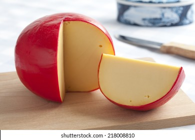 Edam cheese and a piece on a cutting board