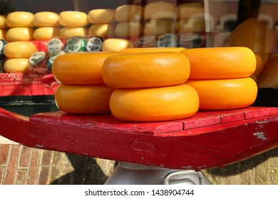 Edam cheese wheels at edam Netherlands cheese market store on a red wooden try and old milk can