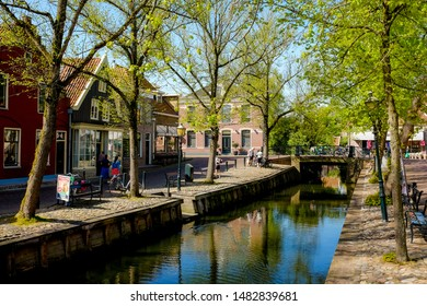 EDAM, THE NETHERLANDS - APRIL 24, 2019: A peaceful street with a bridge crossing over the small beautiful canal and people walking along in the town of Edam, the Netherlands.