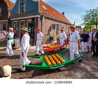 Edam, Netherlands, July 2018. Men in traditional white clothing, carrying Yokes with Edam cheese in a parade through the streets during the cheese market