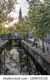 Edam, The Netherlands, October 7, 2018: view from Dam square along Voorhaven canal towards the tower of Kleine Kerk (Small Church) in autumn
