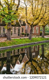 Edam, The Netherlands, October 7, 2018: canal houses with wooden and brick facades and trees in autumn colors reflecting in the calm water of the IJe canal