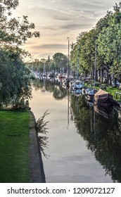 Edam, The Netherlands, October 7, 2018: yachts and historic barges moored at Nieuwehaven canal and reflecting in the still waters on a day in autumn
