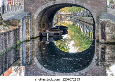 Edam, The Netherlands, October 7, 2018: two sloops moored under the brick arch of the bridge across Voorhaven canal at Dam square