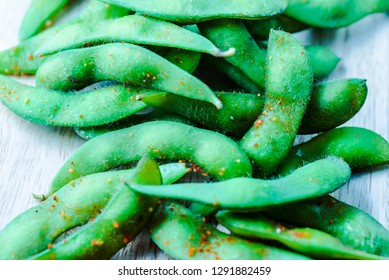 Edamame beans in artistic colorful processing. Edamame beans in salt and spices. Boiled immature soybeans in pods on a wooden cutting board with blurred background. Asian traditional food. Macro food