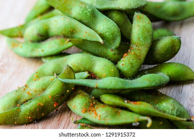 Edamame beans in salt and spices. Boiled immature soybeans in pods on a wooden cutting board with blurred background. Asian traditional food. Macro food photo for cafe, menu, restaurant, design
