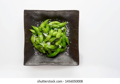 Edamame green soybeans in the bowl, fried green soybeans with salt in a black bowl on white background