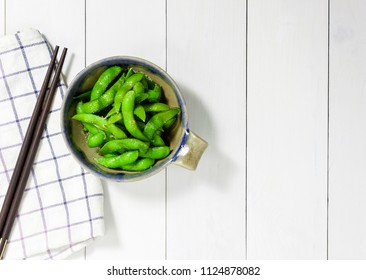 edamame nibbles, boiled green soy beans, japanese food, Top view on white wooden table