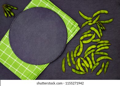 Edamame soy pods cooking background with round slate plate, green napkin, green soy pods on black slate background, copy space, text place. Edamame  frame