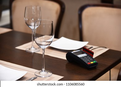 EDC machine or bankcard in reader on table in restaurant. Credit card terminal near glasses and plates on table background. Payment with credit card. Electronic finance and shopping concept.
