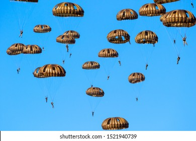 EDE, NETHERLANDS - SEP 21, 2019: Group of military parachutist paratroopers in the sky during the Operation Market Garden memorial.