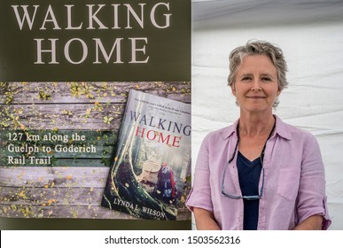 EDEN MILLS, ONTARIO, CANADA - SEPTEMBER 8, 2019: Author Lynda Wilson stands before of her outdoor book display at the annual Eden Mills Writers Festival.