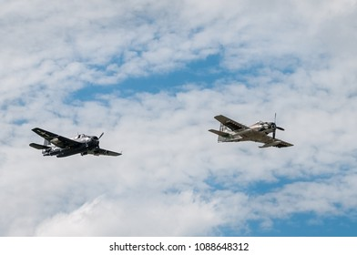 EDEN PRAIRIE, MN - JULY 16, 2016: Avenger and Skyraider fly across cloudy sky at air show. The torpedo bomber and attack aircraft were both used from WWII up until the 1960s and 80s.