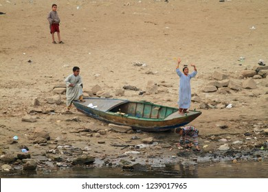 EDFU, EGYPT - DECEMBER 29, 2011: Egyptian kids playing on a small rowing boat on the Nile shore, around Edfu, High Egypt.
