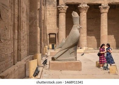 EDFU, EGYPT - JUNE 6, 2019: Two female tourists making selfies in front of statue of Horus in  the Ptolemaic Temple of Horus in Edfu