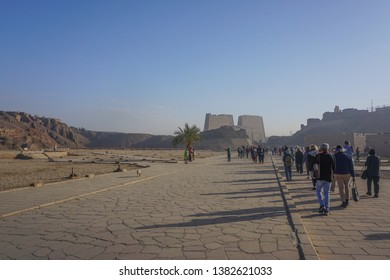 Edfu / Egypt - March 13, 2019: Visitors approach the entrance to the temple of Edfu, the largest temple dedicated to Horus and Hathor of Dendera, on a misty morning.