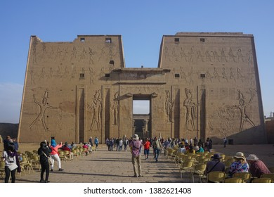 Edfu / Egypt - March 13, 2019: Guests relax in chairs or photograph the first pylon of the temple of Edfu, the largest temple dedicated to Horus and Hathor of Dendera.