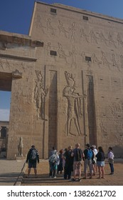 Edfu / Egypt - March 13, 2019: Tourists and their guide at the first pylon of the temple of Edfu, the largest temple dedicated to Horus and Hathor of Dendera.