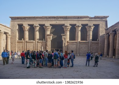 Edfu / Egypt - March 13, 2019: Tourists listen to their guide in the courtyard of the temple of Edfu, the largest temple dedicated to Horus and Hathor of Dendera.