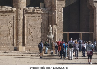 Edfu / Egypt - March 13, 2019: Tourists wait in line to be photographed with a statue of Horus at the temple of Edfu, the the largest temple dedicated to Horus.