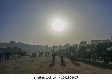 Edfu / Egypt - March 13, 2019: Visitors arrive by horse cab at the plaza near the entrance to the Edfu temple dedicated to Horus, under a bright morning sun.