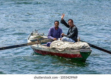 EDFU, EGYPT - MARCH 17, 2010 : A couple of friendly Egyptian men row their wooden boat on the River Nile near Edfu in Egypt.