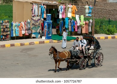 EDFU, EGYPT - MARCH 17, 2010 : A horse and buggy ferry a group of foreign tourists past a textile shop on a street in the Egyptian town of Edfu.
