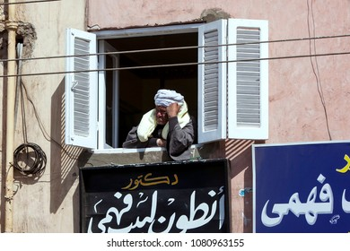 EDFU, EGYPT - MARCH 17, 2010 : An Egyptian man surveys the busy steets of Edfu in Egypt from a shuttered window in an apartment building.