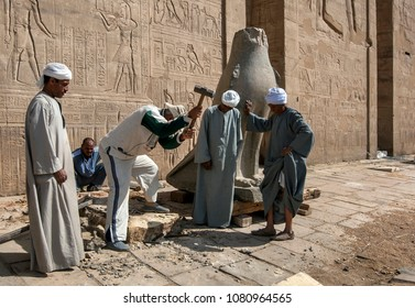EDFU, EGYPT - MARCH 17, 2010 : Workers at the Temple of Horus at Edfu making a new base for one of the carved stone falcons at the pylon entrance. The temple was constructed by Ptolemy III in 237 BC.