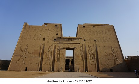 EDFU, EGYPT - OCTOBER 1, 2018: The main entrance of Edfu Temple showing the first pylon, Dedicated to the Falcon God Horus, Located on the west bank of the Nile, Edfu, Upper Egypt